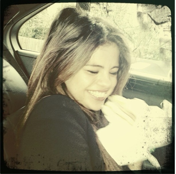 Check out this photo of Selena Gomez giggle-eating a McDonald's Egg McMuffin.